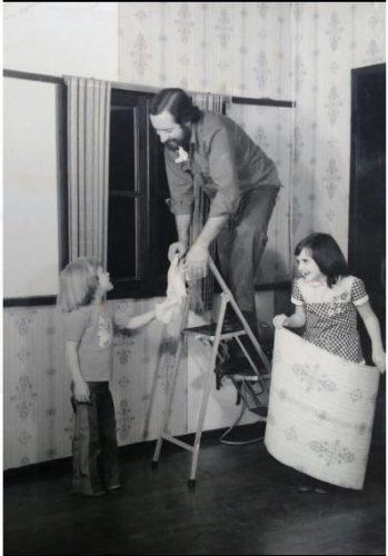 Catia Badia com seu irmão ajudando ao pai colocar um papel de parede.