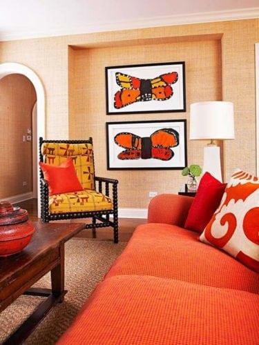 Sala com sofá laranja e quadros com borboletas.