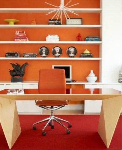 Estante no escritório com o fundo pintado de laranja.
