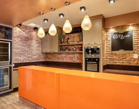 Cozinha com parede em tijolinhos e ilha laranja.