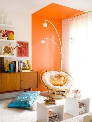 Sala com cantinho decorado com uma faixa laranja pintada na parede.