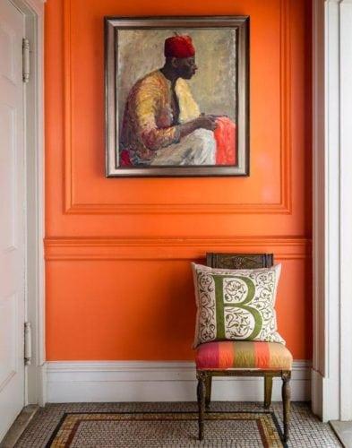Hall de entrada decorado com lambri na parede toda pintada de laranja.