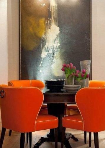 Sala de jantar com mesa redonda e cadeiras laranja.