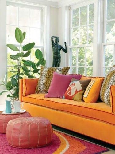 Sofá laranja com almofadas de onça.