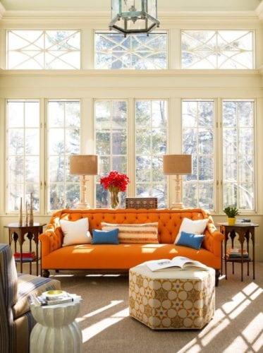 Sala com sofá laranja.