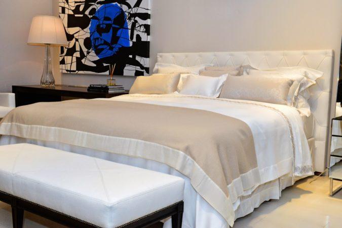 Quarto decorado com roupas de cama clara, branca e bege.