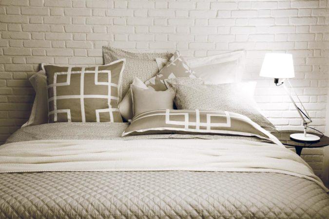 Quarto com parede em tijolinho branco e cama forrada com lençol branco e bege.