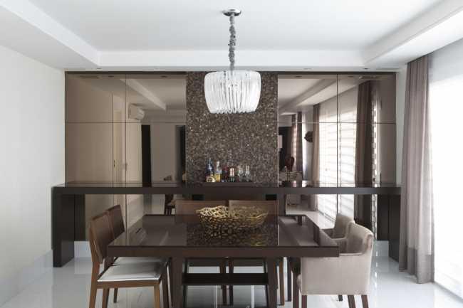 Sala de jantar com duas faixas de espelhos na cor bronze .