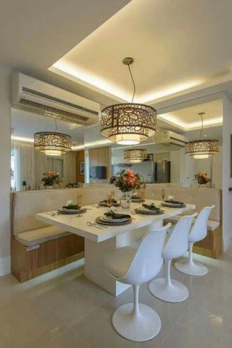 Canto da sala de jantar com espelhos em duas paredes, fazendo um L aumentando a profundidade.