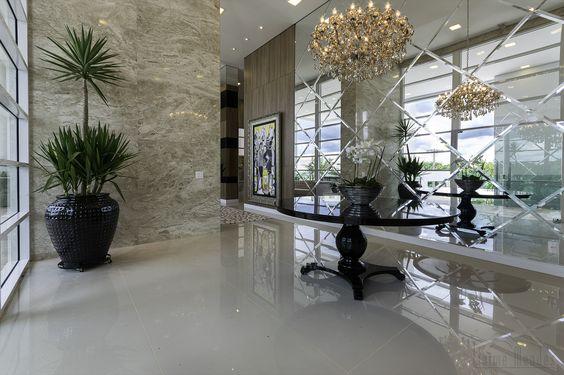 Hall de entrada com pé direito alto , recebeu uma parede de espelhos com placas diagonais bisotadas.