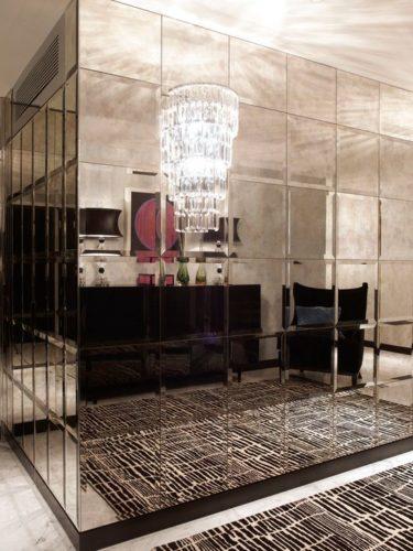 Hall de entrada com as paredes em quina revestidas de espelhos bronze bisotados quadrados.