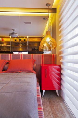 Frigobar na decoração, usado como mesa lateral da cama na cor vermelha destaque do quarto.
