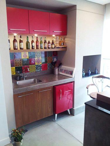 Frigobar na decoração, armários superiores na mesma cor do frigobar embaixo da bancada. Varanda com churrasqueira.