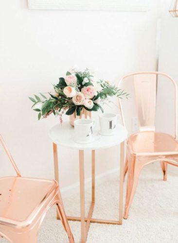 Rose Gold ou cobre na decoração, cadeiras em rose gold e mesa tampo em vidro branco e pés em rose gold.