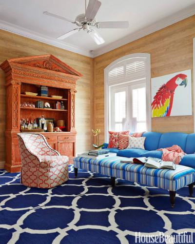 tapete azul e branco com sofa azul claro e quadro de arara vermelha