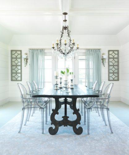 Sala de jantar com mesa preta e cadeiras em acrílico transparentes de Philippe Starck.