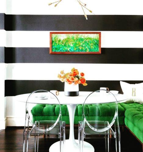 Ambiente com paredes listradas de preto e branco, sofá verde e cadeiras em acrílico transparente de Philippe Starck.