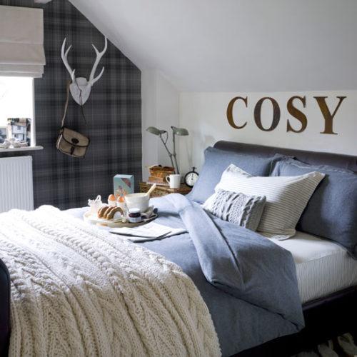 quarto com tecido na parede e a palavra COSY