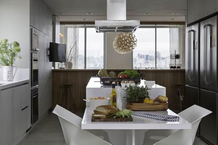 Projeto Roberta Devisate COZINHA | A pequena mesa para refeições rápidas está acoplada à ilha com cadeiras de polipropileno, da Novo Ambiente. Todas as bancadas foram executadas com Silestone branco