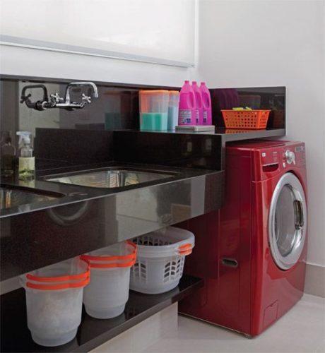 maquina de lavar vermelha e marmore preto na area de serviço