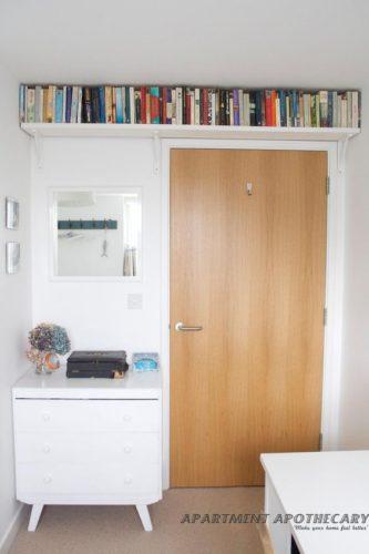 Biblioteca em casa, decorando com livros.Prateleira em cima da porta para guardar os livros.