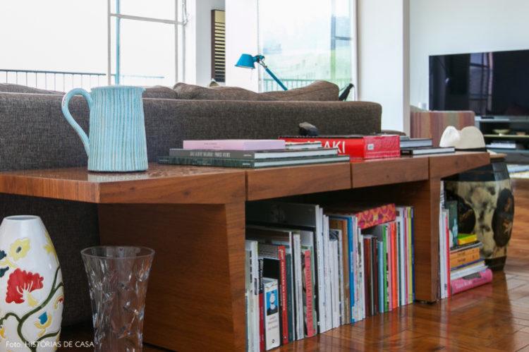 Biblioteca em casa, decorando com livros. Banco atras do sofá com livros.