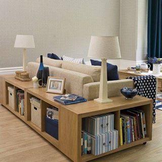 Biblioteca em casa, decorando com livros. Atrás do sofá, pequena estante/modulo para livros.