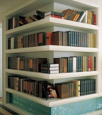 Biblioteca em casa, decorando com livros. Estante em quina da parede abriga a biblioteca da casa.