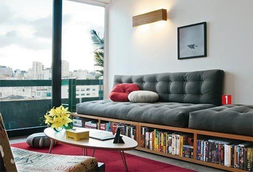 Biblioteca em casa, decorando com livros. Sofá de futons em cima da base de madeira para guardar livros.