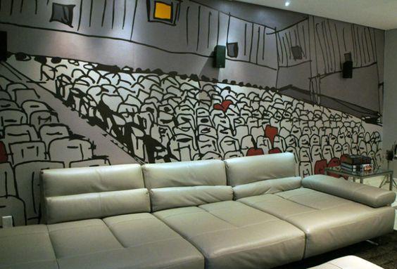 Sofá confortável para assistir filmes e decoração da sala com o papel imitando uma sala de cinema.