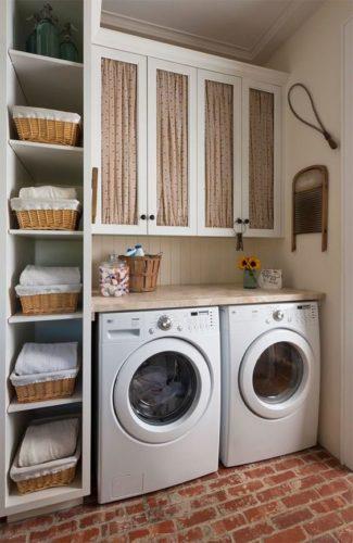 Lavanderia decorada com cestos de palha e cortininha no armário superior.