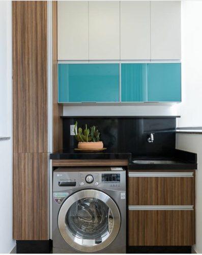 Lavanderia e área de serviço decorada com armários em branco, azul e madeira.