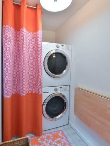 Lavanderia decorada, box que não é usado recebe uma cortina charmosa para esconder as máquinas.