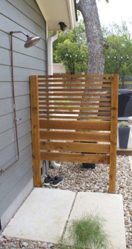 Chuveiro na lateral da casa com divisória de madeira ripada