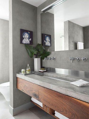 banheiro com bancada, parede e piso com cimento queimado