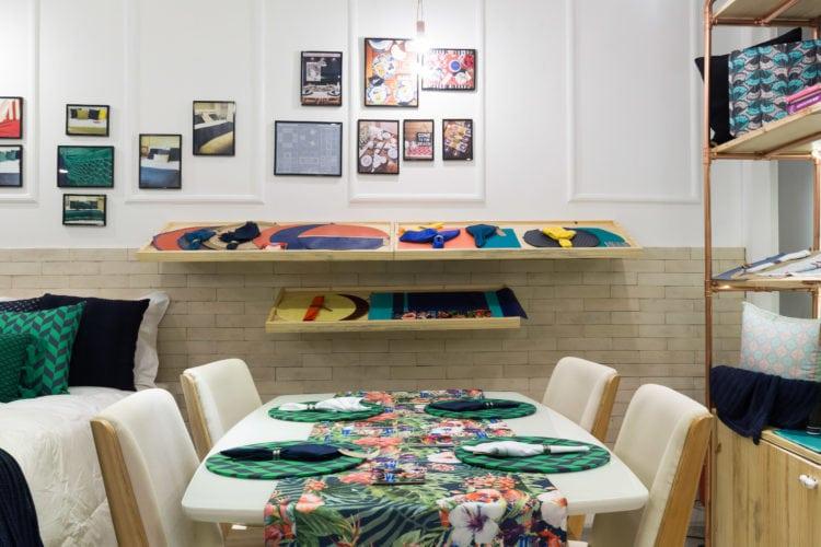 Soluções criativas, com baixo custo e design arrojado by Paula Werneck. expositores para os jogos americanos e o tijolinho aparente para delimitar os espaços.