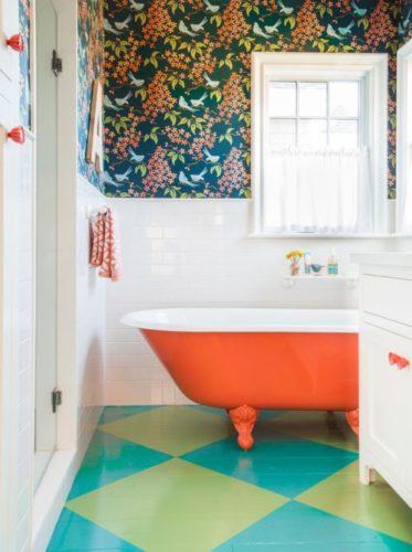 Banheiro decorado por Alison Kandler, piso xadrez em azul e verde com banheira laranja.