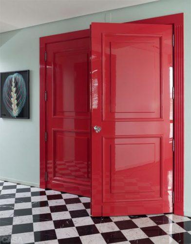 Porta de entrada da casa pintada de cereja e piso xadrez