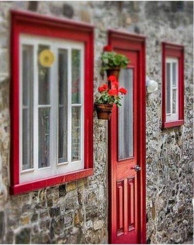 Portas de entradas coloridas. Porta e janela vermelha na fachada de pedras.