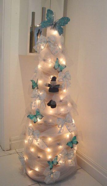 Árvore de Natal branca, enfeitadas com borboletas azuis.