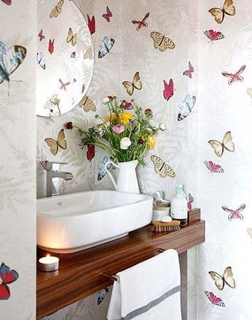 Lavabo decorado com papel de parede de borboletas.