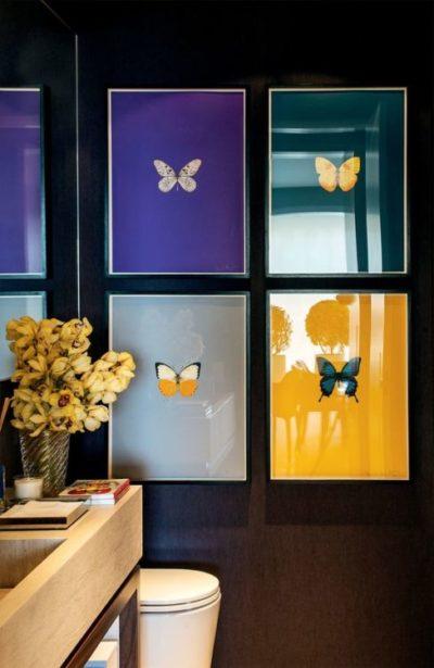 Lavabo decorado com quadros de borboletas com fundo colorido. Contraste bonito na parede preta.