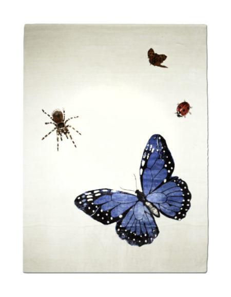 Tapete com insetos estampados e uma borboleta azul grande. Da By Kami tapetes.