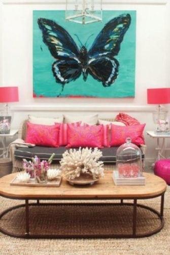 Sala com almofadas rosas no sofá e uma tela turquesa com uma borboleta na parede atrás do sofá.. Contraste .