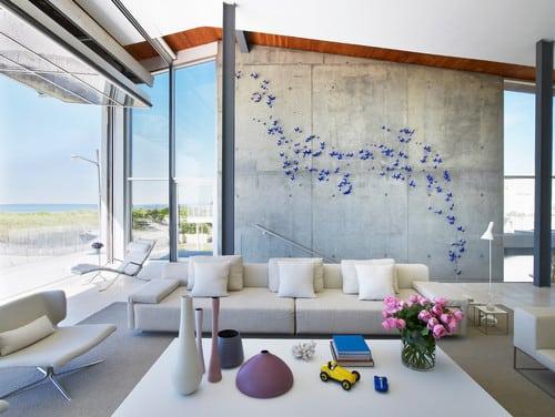 Decoração contemporânea, borboletas azuis enfeitam a parede de concreto na sala.