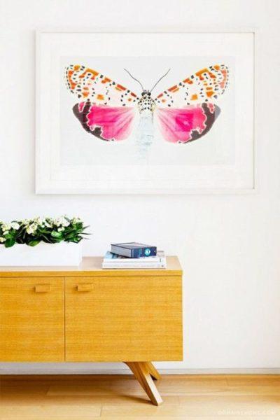 Quadro com borboleta rosa decorando a parede .