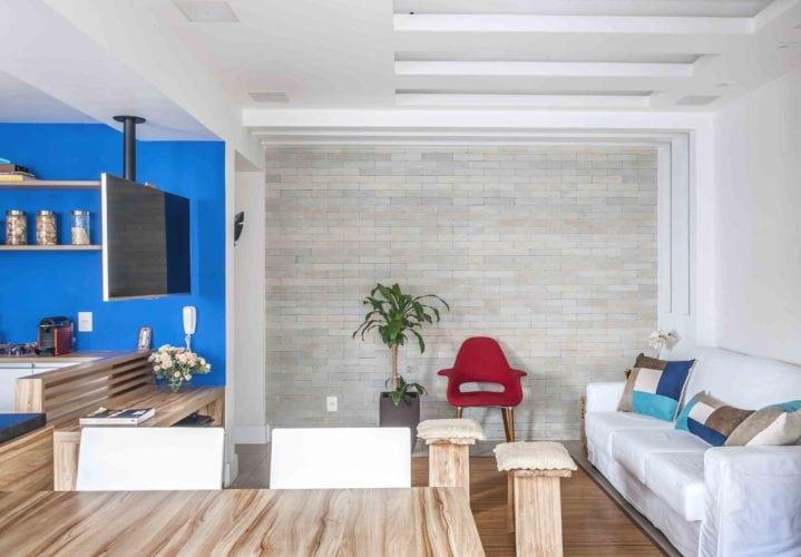 Apartamento com sala, sala de jantar e cozinha integrados. Televisão com suporte giratório no teto, alcança todos os ambientes.