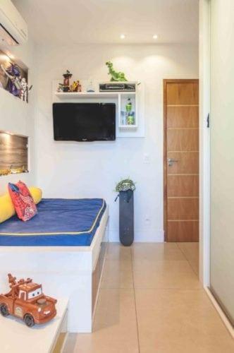 Apartamento otimizado, quarto de menino com tv na parede e na lateral da cama.