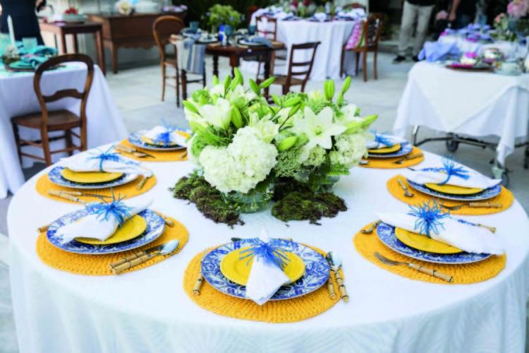 Inspirações para se criar mesas caprichadas, mesa redonda com arranjo de flor baixo e louça azul com jogo americano amarelo