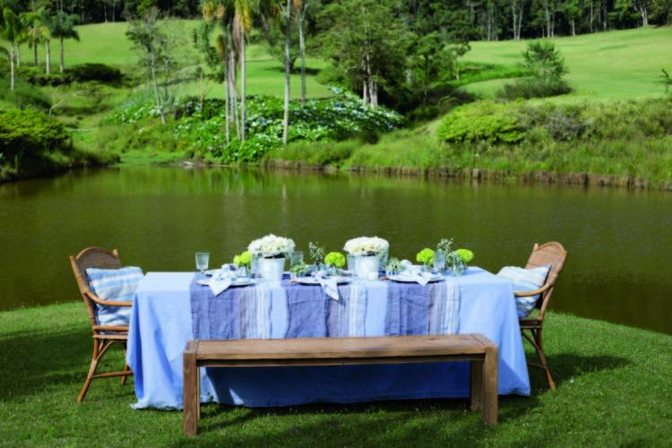 Inspirações para se criar mesas caprichadas. Mesa rustica com toalha azul de linho e banco, no meio do gramado na beira do lago.